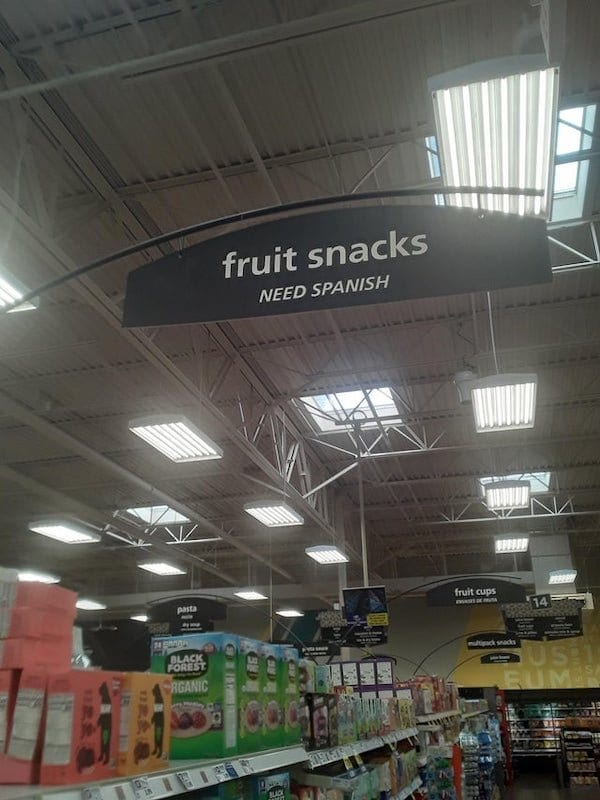 Grocery aisle sign reads 'fruit snacks' and then underneath 'need Spanish'.